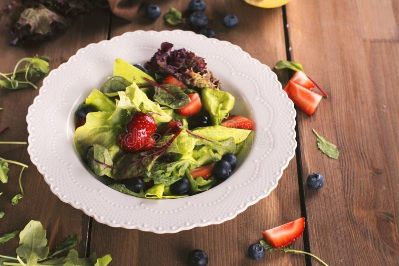 Frischer Sommersalat mit Beeren und Grünblättern lizenzfreies stockbild