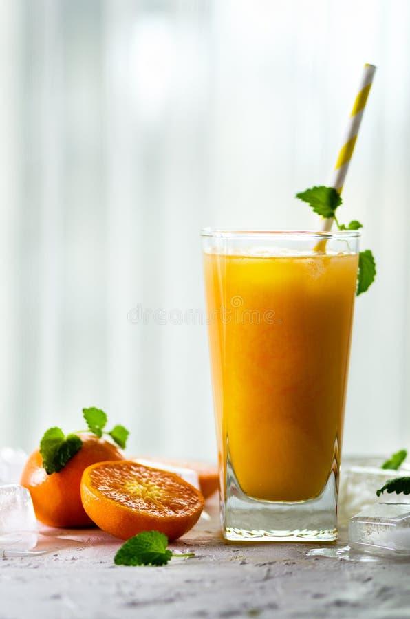 Frischer Tangerinesaft im Glas auf weißem konkretem Hintergrund Orange Früchte mit Eis, Minze Kaltes Getränk für heißen Sommer lizenzfreies stockbild