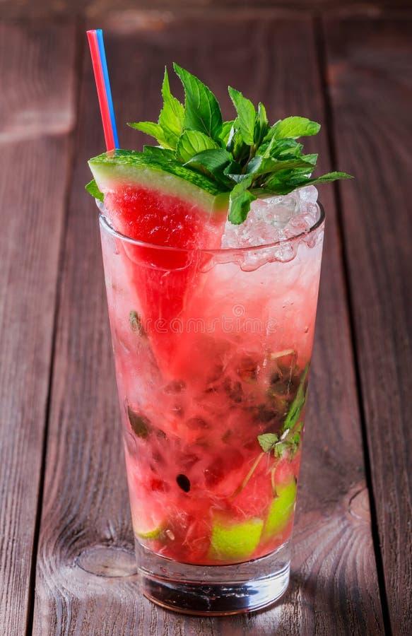 Frischer Wassermelonengetränk Smoothie mit Minze, Eis und Kalk im Glas auf hölzernem Hintergrund stockbilder