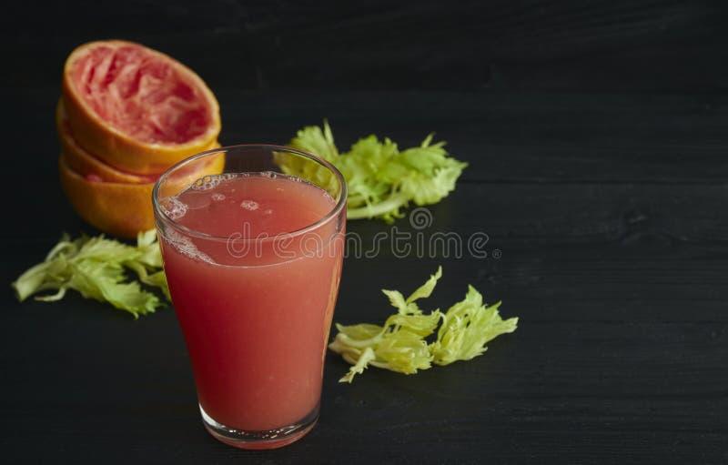 Frischer ZitrusfruchtGrapefruitsaft in einem Glas Auf einem schwarzen Holztisch Schwarzer Hintergrund Horizontale Ansicht Platz f stockfotografie