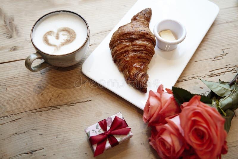 Frisches Bäckereihörnchen, Kaffee mit Herzzeichen, rosafarbene Blumen auf Holztisch Romantisches Frühstück für Valentinsgruß ` s  lizenzfreie stockbilder