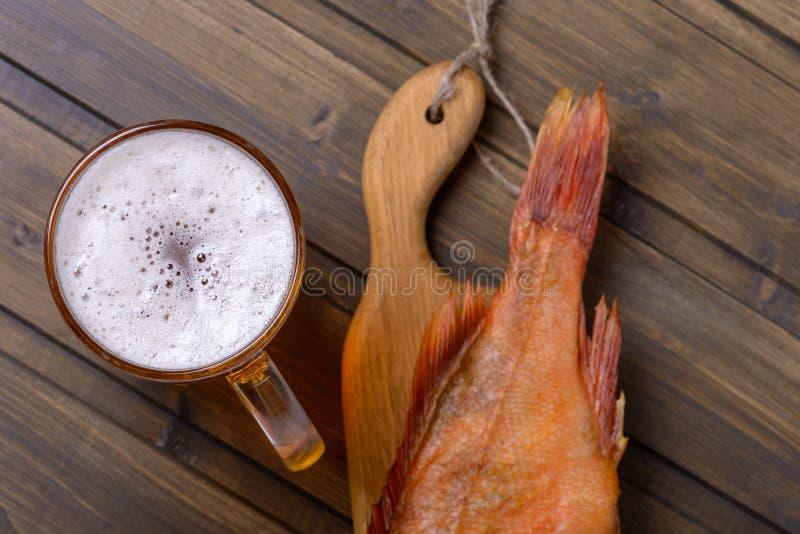 Frisches Bier der Nahaufnahme mit Fischen auf Holztisch in der Kneipe stockfoto