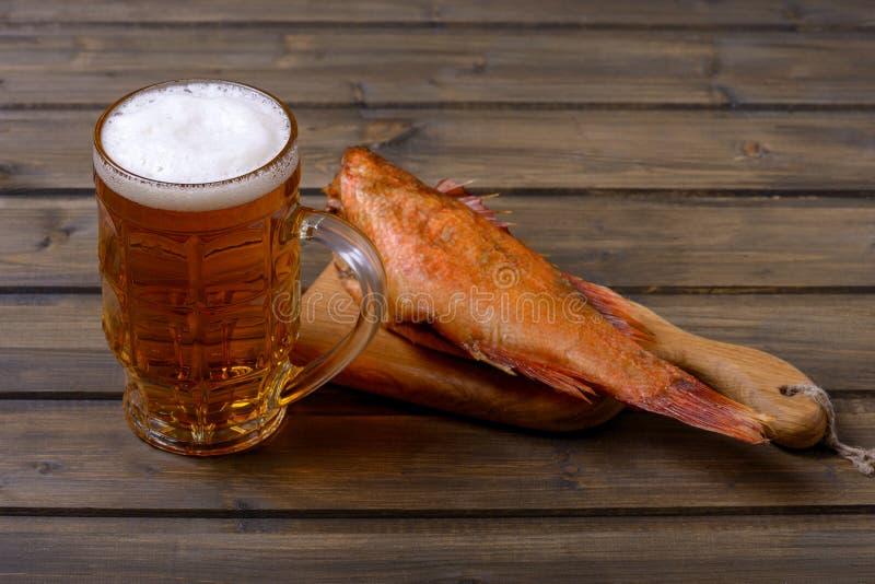 Frisches Bier im Becher mit Schaum und geräucherten Fischen stockbild