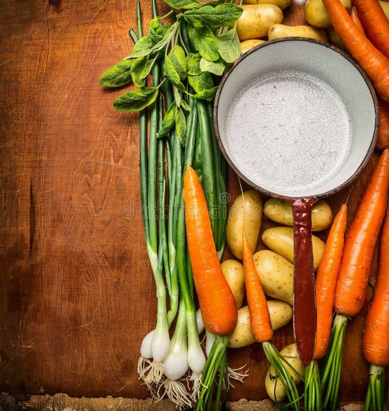 Frisches Biogartengemüse um leere alte kochende Wanne auf hölzernem Hintergrund, Draufsicht lizenzfreies stockbild