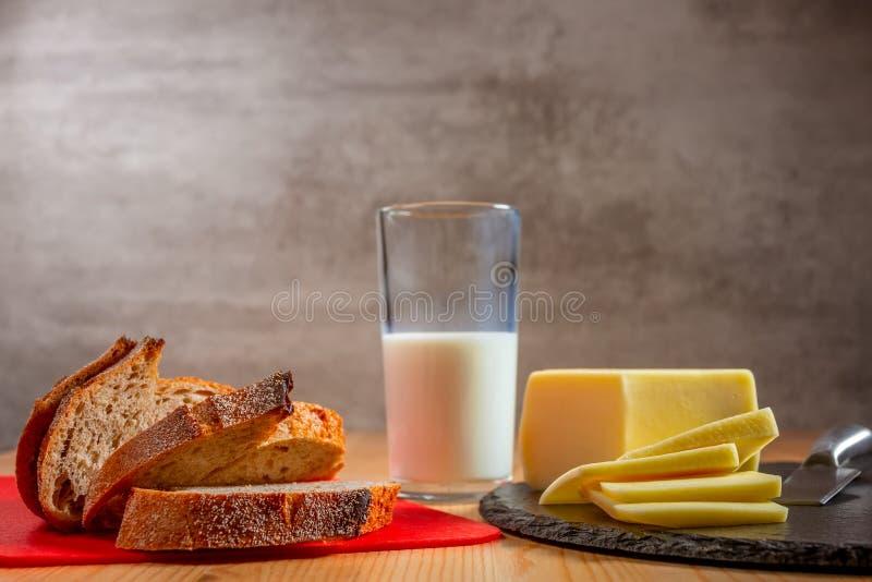 Frisches Brot, Käse und Milchglas stockbild