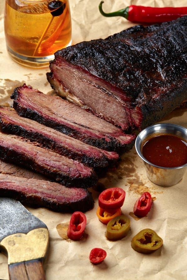 Frisches Bruststück BBQ-Rindfleisch geschnitten für das Dienen gegen einen Kraftpapierhintergrund mit Soße, Peperoni und Mais stockbild