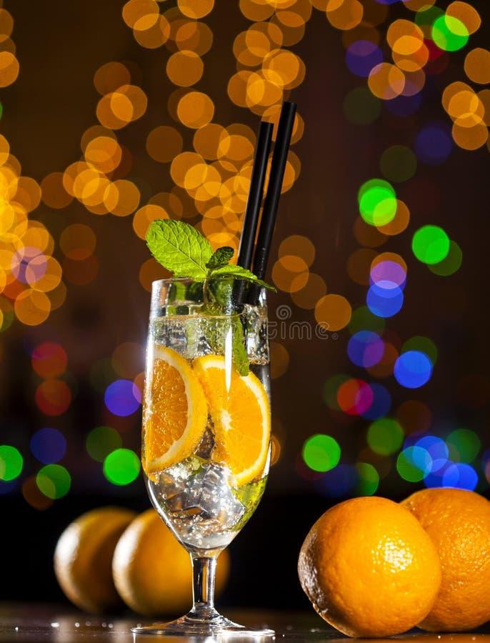 Frisches Cocktail mit Orange, tadellose Blätter Eis-ANG auf Bar beleuchtet Hintergrund stockbilder