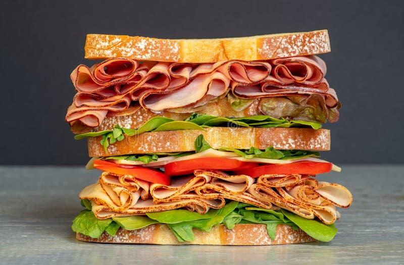 Frisches doppeltes überlagertes Sandwich mit Schinken, Kopfsalat, Tomaten, Käse auf einem Toastbrot, auf schwarzem Hintergrund stockfoto