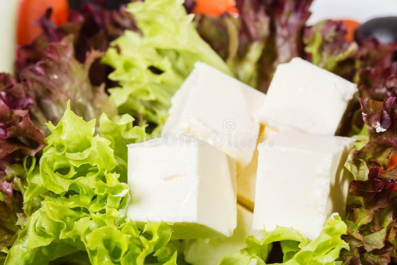 Frisches Feta auf Kopfsalatblättern stockbild