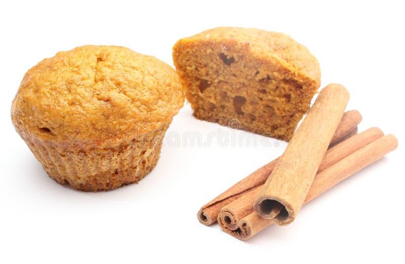 Frisches gebackenes Karottenmuffin und -Zimtstangen. Weißer Hintergrund lizenzfreie stockfotos