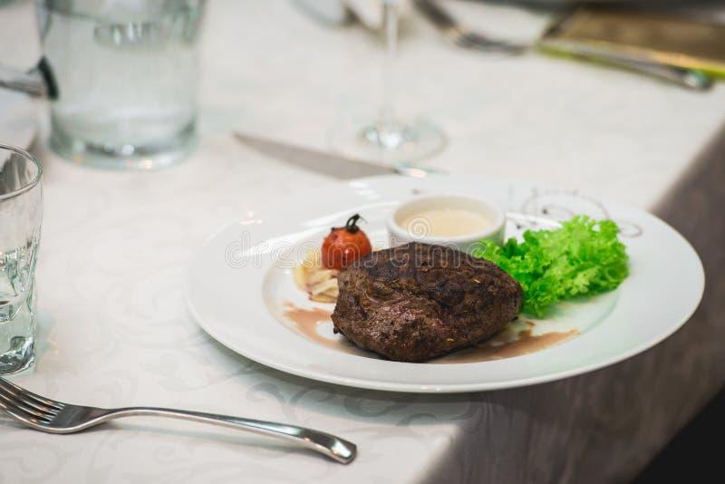 Frisches gegrilltes bbq-Roastbeefsteak und -soße auf einer weißen Platte mit grünem Blatt des Salats Suppensoße kleines Krugglas lizenzfreie stockbilder