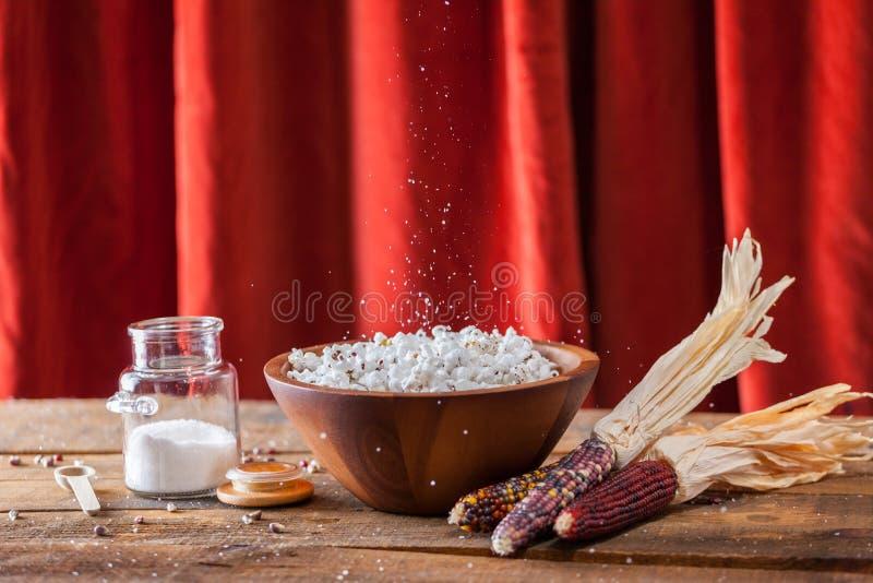Frisches geknalltes Popcorn in der hölzernen Schüssel mit Kernen und Maiskolben auf W stockbild