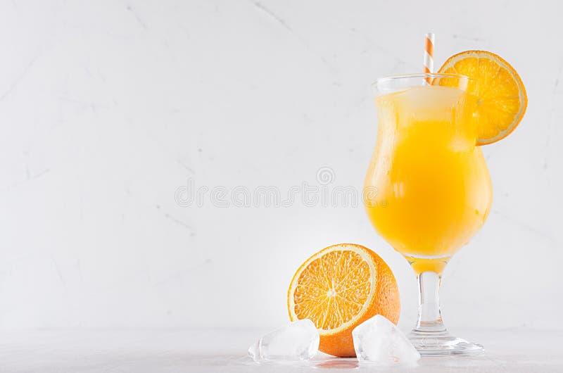 Frisches gelbes Orangencocktail im Eleganzweinglas mit Eiswürfeln, Stroh und halben Orangen auf weichem weißem hölzernem Hintergr stockfotografie