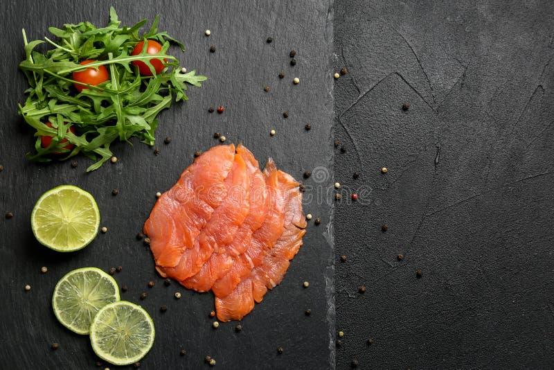 Frisches geschnittenes Lachsfilet mit Arugula und Zitrone auf Schieferplatte, Draufsicht stockbild