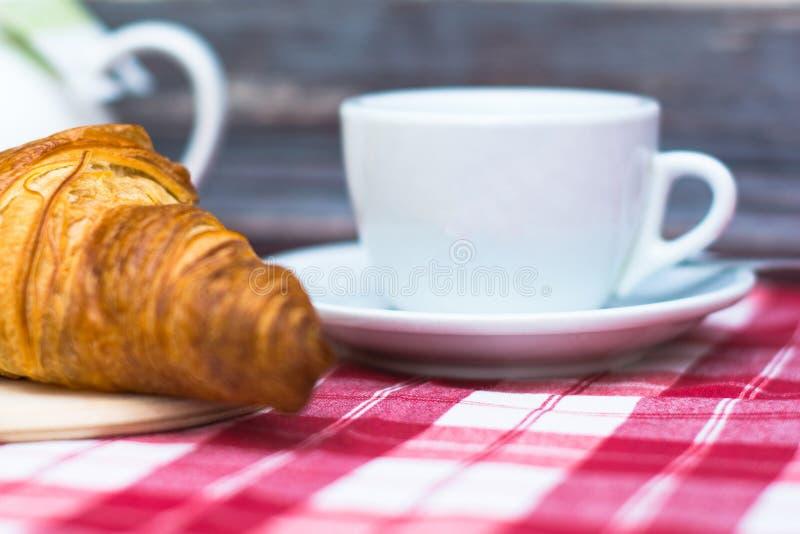 Frisches Hörnchen und ein weißer Tasse Kaffee auf einer roten weißen karierten Tischdecke nahe einer hölzernen Wand Französische  stockfotografie