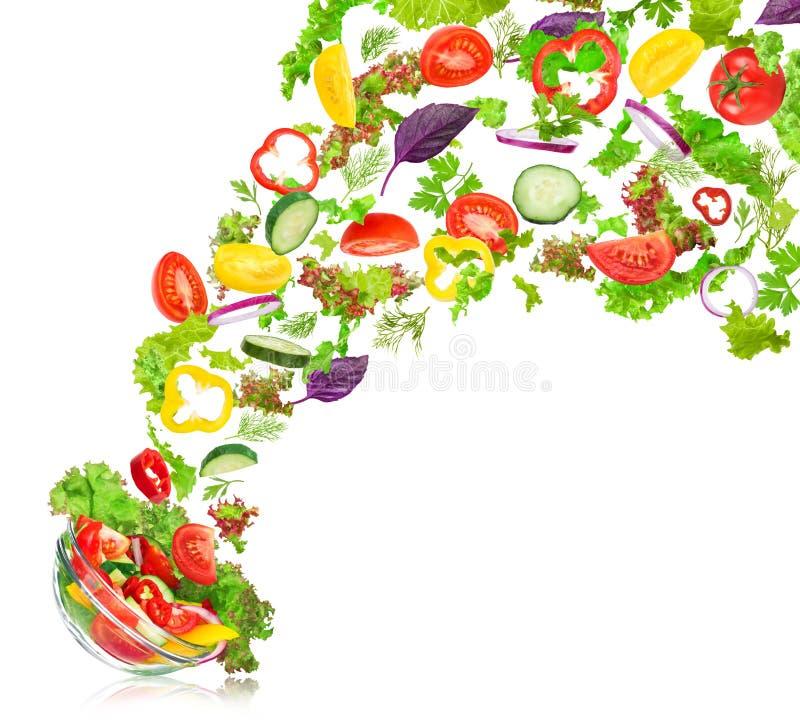 Frisches Mischgemüse, das in eine Schüssel Salat fällt stockbild