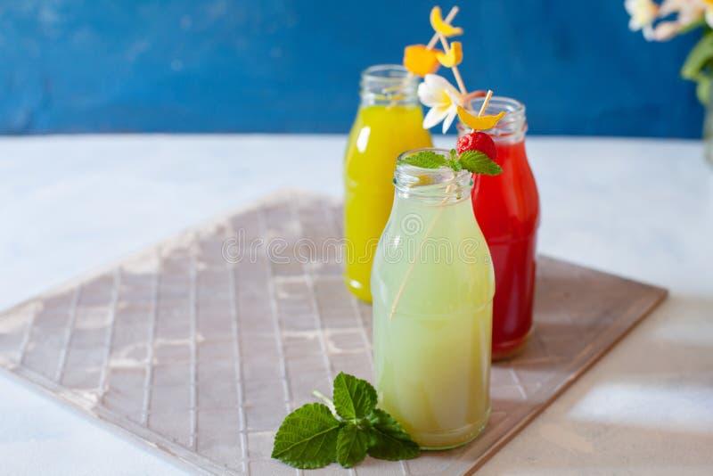 Frisches Obst, Beeren und Gemüsesaft auf hellblauem Hintergrund Eigenes erfrischendes Getränk lizenzfreie stockfotos