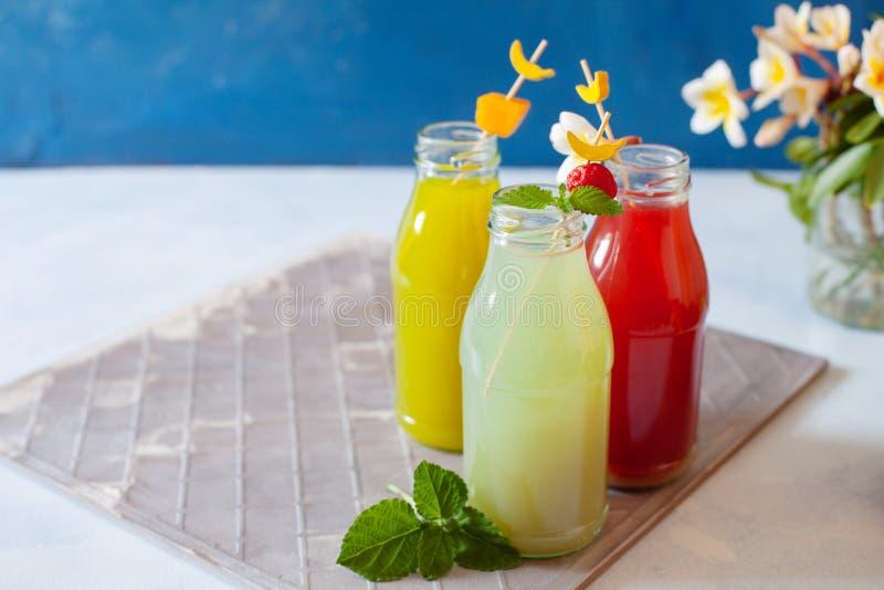 Frisches Obst, Beeren und Gemüsesaft auf hellblauem Hintergrund Eigenes erfrischendes Getränk lizenzfreies stockfoto