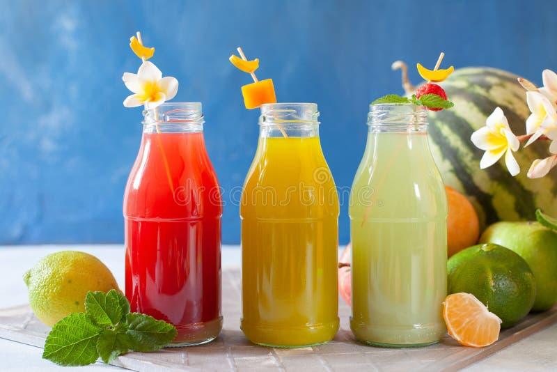 Frisches Obst, Beeren und Gemüsesaft auf hellblauem Hintergrund Eigenes erfrischendes Getränk lizenzfreie stockfotografie