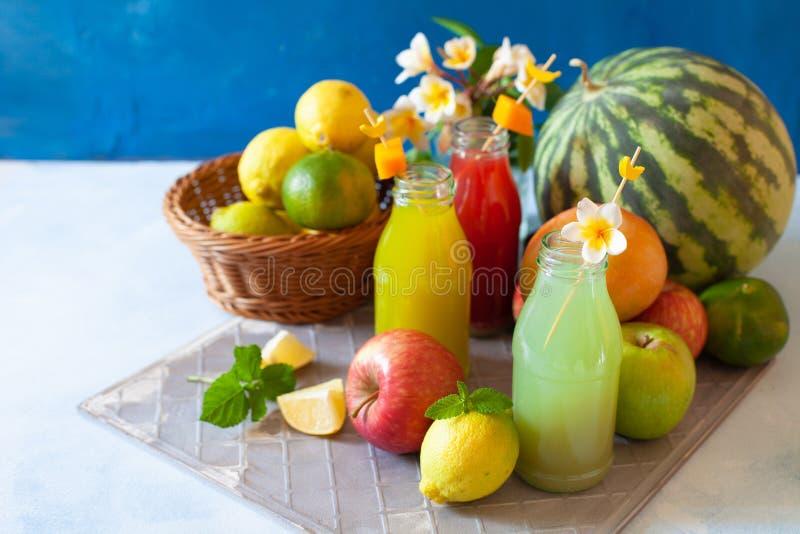 Frisches Obst, Beeren und Gemüsesaft auf hellblauem Hintergrund Eigenes erfrischendes Getränk lizenzfreie stockbilder