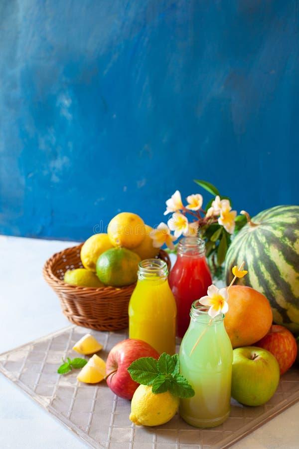 Frisches Obst, Beeren und Gemüsesaft auf hellblauem Hintergrund Eigenes erfrischendes Getränk stockfotografie