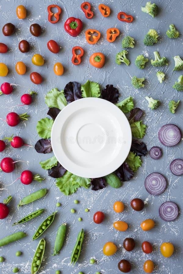 Frisches organisches Gemüse mit weißer Platte auf Tabelle Draufsicht der grünen Erbsen, des Brokkolis, der Zwiebel, der Tomate un stockfoto