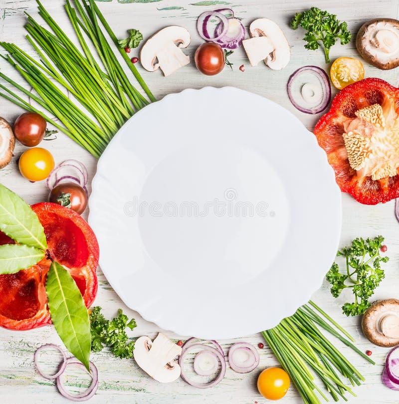 Frisches organisches Gemüse und Gewürzbestandteile für den geschmackvollen Vegetarier, der um leere weiße Platte, Draufsicht koch stockbilder