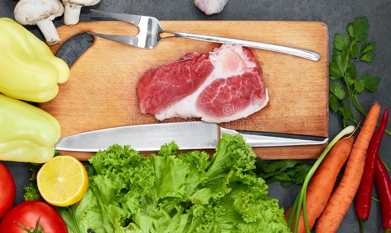 Frisches Rindfleischsteak, hölzerner Löffel, Messer und Zusammenstellung des Frischgemüses, aromatische Kräuter, Gewürze und Gemü stockfotografie