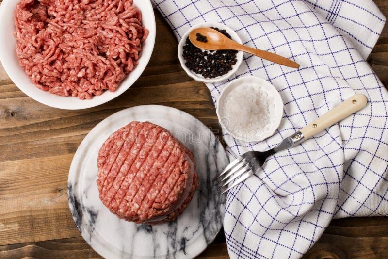 Frisches rohes Burgerpastetchen auf Marmor stockfotografie