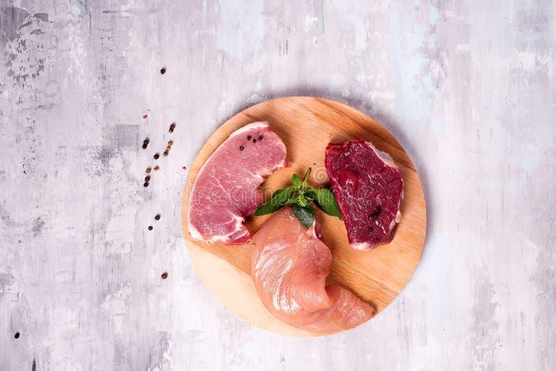 Frisches rohes Fleisch - Rindfleisch, Schweinefleisch und Huhn auf einem hölzernen Hintergrund Magere Proteine lizenzfreie stockfotografie