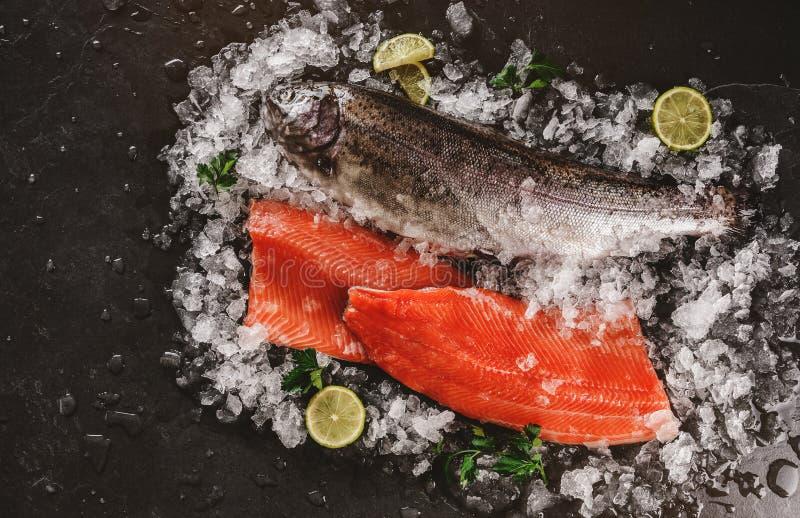 Frisches rohes Forellenfischsteak und ganze Fische mit Gewürzen auf Eis über dunklem Steinhintergrund, Nahaufnahme lizenzfreie stockbilder