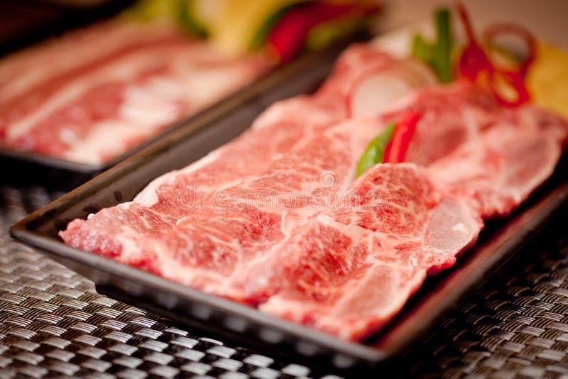 Frisches rohes geschnittenes Rindfleisch mit Paprika auf schwarzem Behälter lizenzfreies stockbild
