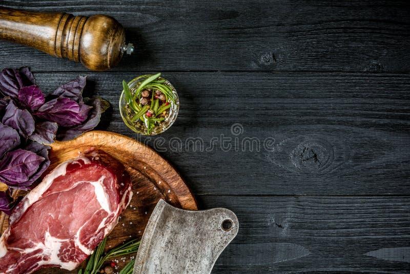 Frisches rohes Rindfleisch mit Basilikum und ein Zweig des Rosmarins mit Axt für Fleisch auf schwarzem hölzernem Hintergrund Besc stockfotografie