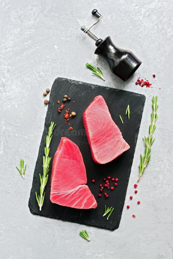 Frisches rohes Thunfischsteak mit Gewürzen auf einer schwarzen Schieferplatte Grauer Hintergrund Draufsicht, flache Lage lizenzfreie stockbilder