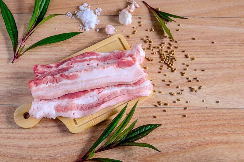 Frisches Schweinefleisch auf einem hölzernen Schneidebrett lizenzfreie stockbilder