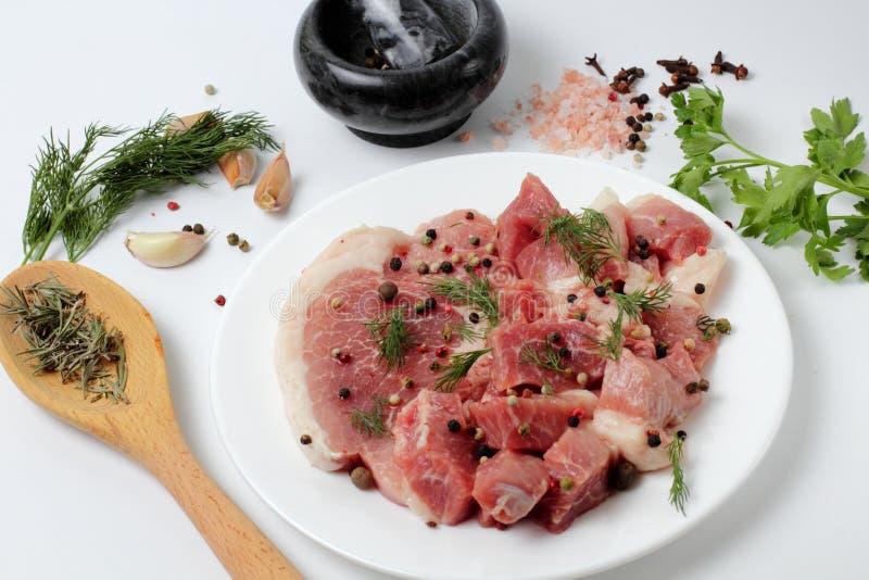 Frisches Schweinefleisch auf einer großen Platte, Gewürze, würzige Kräuter lizenzfreies stockbild