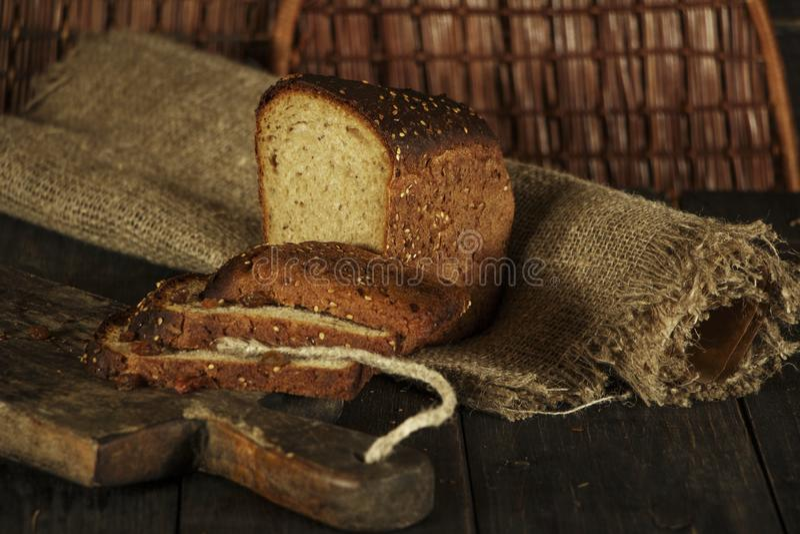 Frisches selbst gemachtes Brot mit Vollweizenspitze auf einem schwarzen hölzernen Hintergrund Frisches Brot mit einem Ohr des Wei lizenzfreie stockfotografie