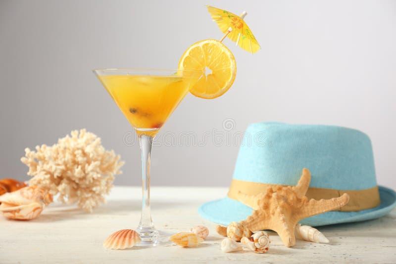 Frisches Sommercocktail im Glas mit Muscheln und im Hut auf Leuchtpult stockbilder