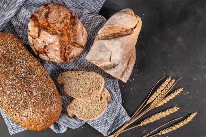 Frisches wohlriechendes Brot auf dem Tisch Chef gießt Olivenöl über frischem Salat in der Gaststätteküche lizenzfreies stockbild