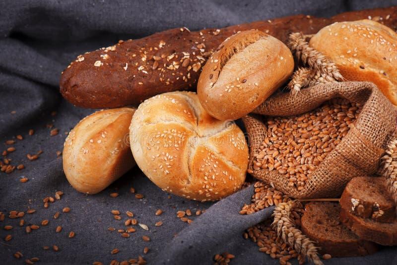 Frisches wohlriechendes Brot auf dem Tisch Chef gießt Olivenöl über frischem Salat in der Gaststätteküche Bäckerei, krustige Brot lizenzfreie stockfotografie