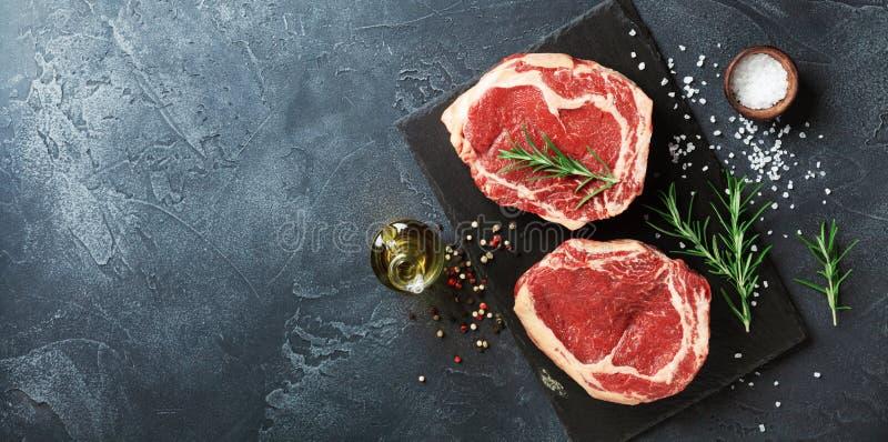 Frischfleisch auf Draufsicht des Schieferschwarzbrettes Rohes Rindfleischsteak und -gewürze für das Kochen lizenzfreie stockbilder