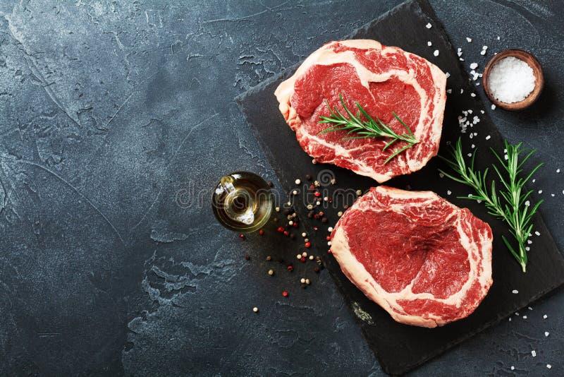 Frischfleisch auf Draufsicht des Schieferschwarzbrettes Rohes Rindfleischsteak und -gewürze für das Kochen lizenzfreie stockfotos