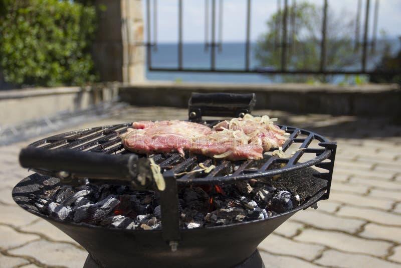Frischfleisch wird auf einem Grill mit Zwiebeln gebraten lizenzfreies stockbild