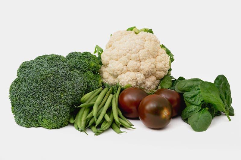 Frischgemüse lokalisiert auf Weiß Blumenkohl, Brokkoli, Bohnen, Tomaten und Spinatsabschluß oben stockfotos