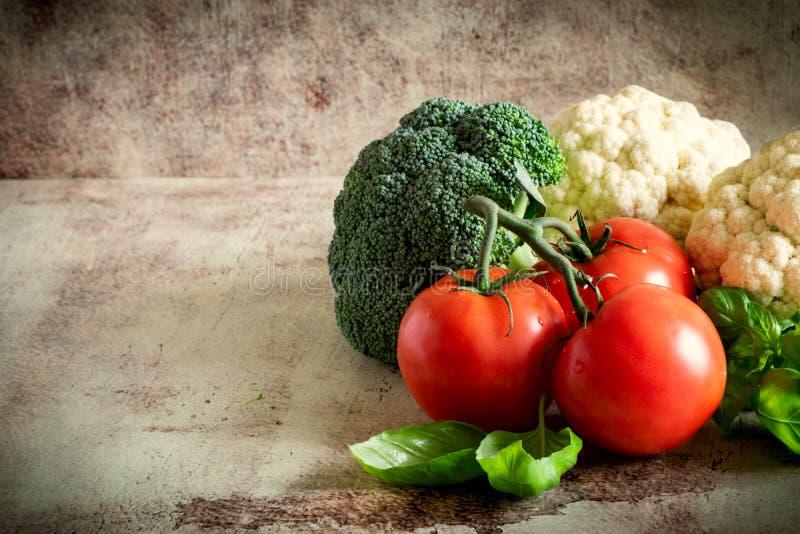 Frischgemüse auf einem grauen Hintergrund: Tomaten, Brokkoli, Blumenkohl und wohlriechender Basilikum stockbilder