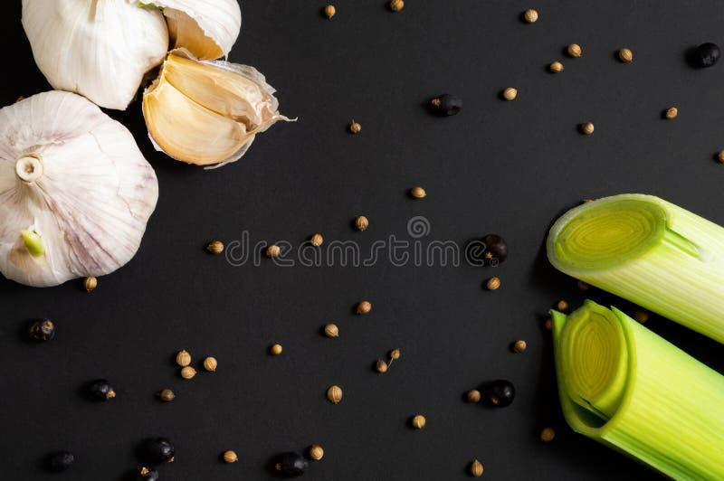 Frischgemüse auf schwarzem Hintergrund: Porree und Knoblauch Verschiedene Gewürze Gesunde Nahrung Flach-Lage, Draufsicht stockbild