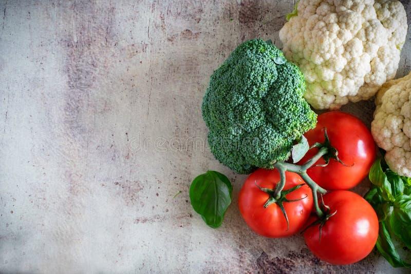 Frischgemüse: Brokkoli, reife Tomaten auf einer Niederlassung, Blumenkohlblütenstände und wohlriechender Basilikum auf einem schö lizenzfreie stockbilder