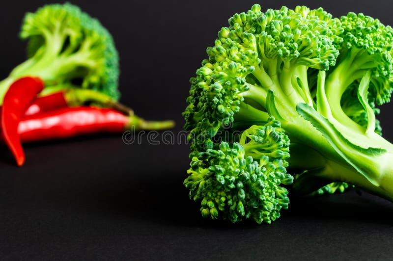 Frischgemüse: Brokkoli und Paprika auf schwarzem Hintergrund Gesunde Nahrung stockfotografie