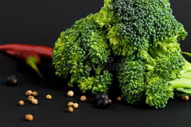 Frischgemüse - Brokkoli und Paprika, verschiedene Gewürze, auf schwarzem Hintergrund Gesunde Nahrung stockbild