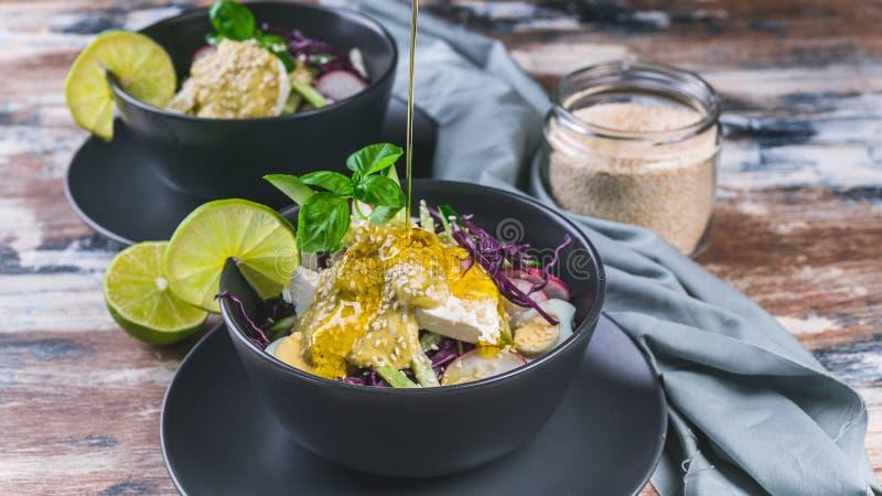 Frischgemüsesalat der Nahaufnahme in einer dunklen Schüssel Salat mit Samen des Rettichs, des Rotkohls, der Gurke, des Pesto und  stockbild